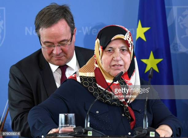 Mevlude Genc mother grandmother and aunt of victims is guided to the lectern by the Premier of North RhineWestphalia Armin Laschet of the Christian...
