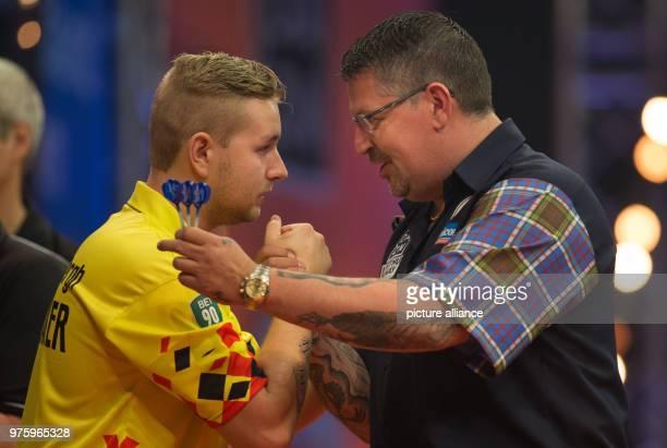 Scottish darts player Gary Anderson congratulates Belgian darts player Dimitri Van den Bergh at the German Darts Masters 2018 of the PDC World Series...