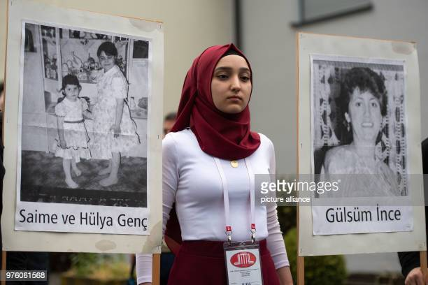 A young woman carries pictures of the victims at the place of the arson attack 25 years after the racially motivated arson attack of Solingen the...