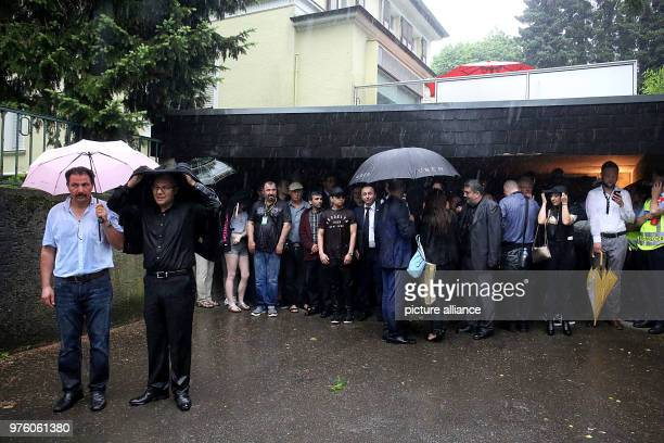 Visitors stand in the rain in the course of the memorial event for the arson attack of Solingen The event had to be cancelled due to a storm 25 years...
