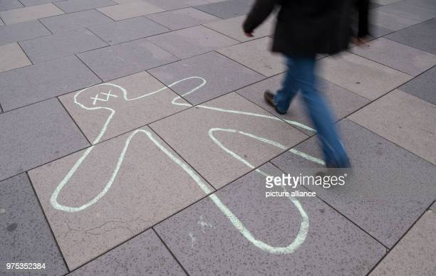 A man walks past the chalk outline of a figure on the pavement which was drawn by opponents of weaponry to symbolize a dead body on the first day of...