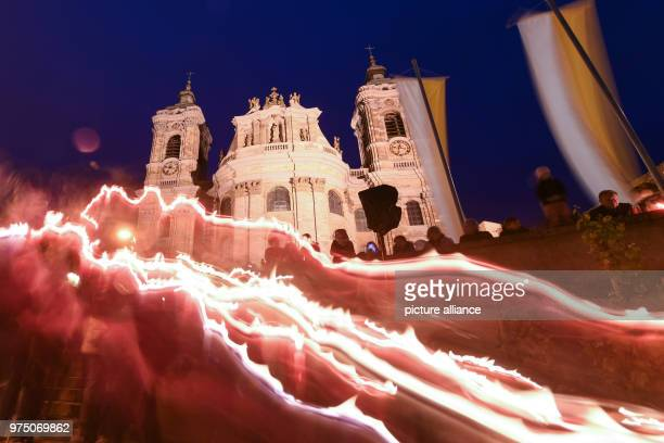 Numerous people walk pass the basilica during a candlelight procession Only light strips can be seen due to the bulb exposure during the blue hour A...