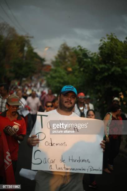 A man holds a banner reading 'We can also expell transnational companies and Palmerola from Honduras' protesting against the TPSdecision of the US to...