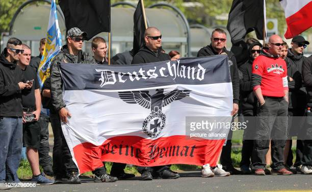May 2018, Saxony, Chemnitz: Participants of a demonstration of right-wing extremists stand with a black-white-red flag on a street. Applicant is the...