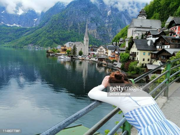 A tourist photographs Lake Hallstatt The World Heritage Community with only 780 citizens is visited by more than one million tourists a year From...