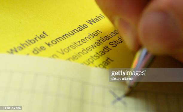 May 2019, Baden-Wuerttemberg, Stuttgart: ILLUSTRATION - A man marks a ballot paper of the postal ballot for the local election in Baden-Württemberg....
