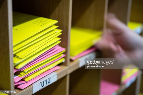 May 2019, Baden-Wuerttemberg, Stuttgart: ILLUSTRATION - A woman puts an election letter for the local election in Baden-Württemberg on a shelf. In...