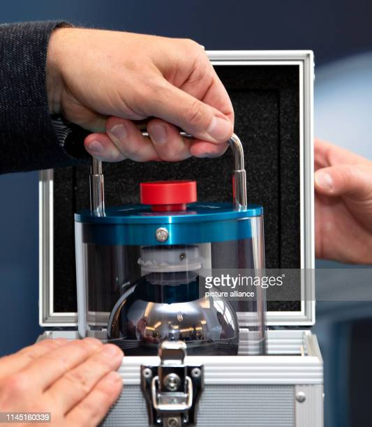 An employee of the PhysikalischTechnische Bundesanstalt fetches a glass cylinder with a highpurity silicon ball weighing exactly one kilogram from a...