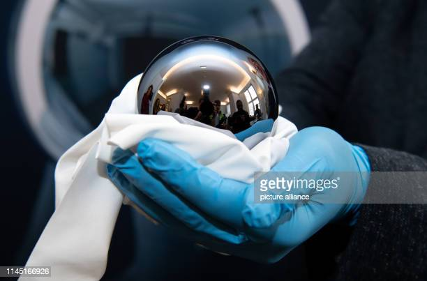 An employee of the PhysikalischTechnische Bundesanstalt is holding a highpurity silicon sphere weighing exactly one kilogram in his hands at the...