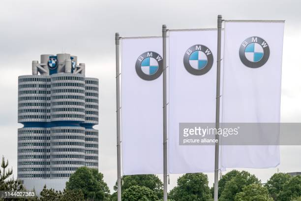 Flags with the logo of the Munich car manufacturer BMW waft in front of the Olympic Hall The BMW headquarters can be seen in the background BMW...