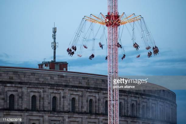 Die Kettenschaukel auf dem Volksfest in der Dämmerung vor der Kulisse der Kongresshalle auf dem ehemaligen Reichsparteitagsgelände Das Nürnberger...