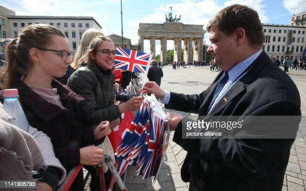 Man distributes British flags to waiting spectators before the arrival of the British heir to the throne at the Brandenburg Gate. Photo: Wolfgang...