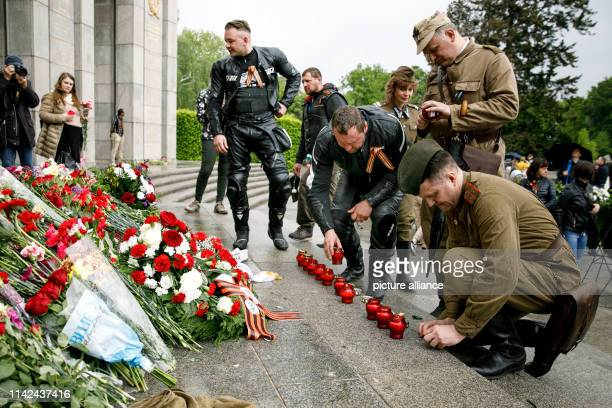 People in traditional uniforms light candles in front of the Soviet Memorial at the Tiergarten on the occasion of the 74th anniversary of Russia's...