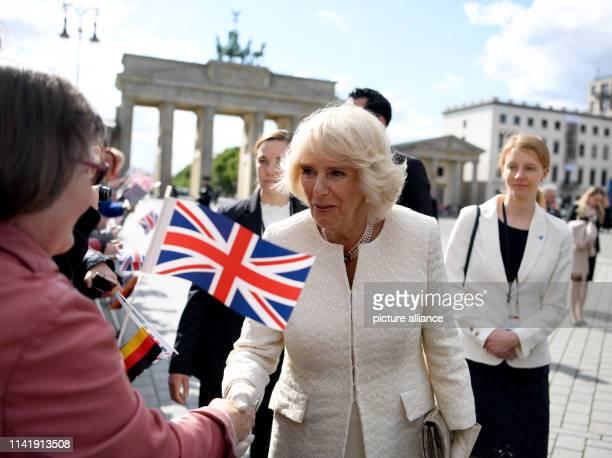 The British Duchess Camilla speaks with spectators in front of the Brandenburg Gate. Photo: Ralf Hirschberger/dpa-Zentralbild/dpa
