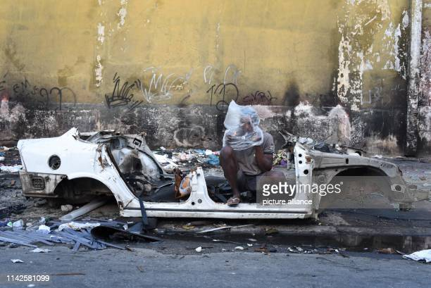 A crack addict smokes in the wreck of a car in Tidal a conglomerate of about a dozen favelas known as Maré The state doesn't have much to report in...