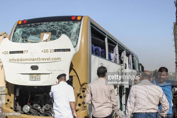 People and security personnel stand next to a damaged tourists' bus at the site where a bomb went off near the Grand Egyptian Museum in GizaAt least...