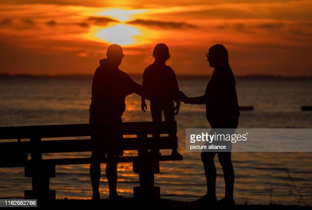 May 2019, Mecklenburg-Western Pomerania, Boek: A family watches the sunset on the banks of the Müritz. Founded in 1990, the Müritz National Park is...