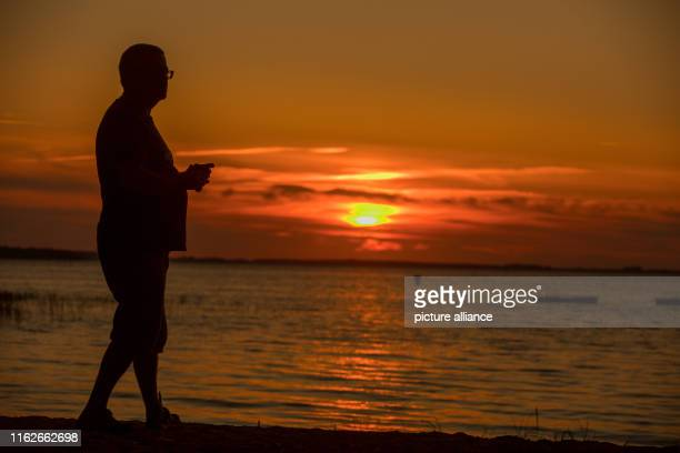May 2019, Mecklenburg-Western Pomerania, Boek: A man watches the sunset on the banks of the Müritz. Founded in 1990, the Müritz National Park is...
