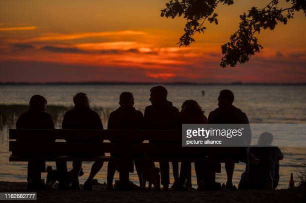 May 2019, Mecklenburg-Western Pomerania, Boek: Holidaymakers sit on a bench on the banks of the Müritz and watch the sunset. Founded in 1990, the...