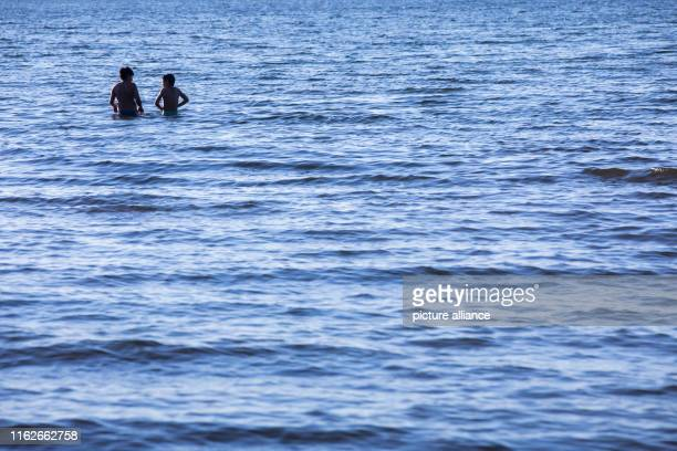May 2019, Mecklenburg-Western Pomerania, Boek: Holidaymakers swim shortly before sunset in the Müritz. Founded in 1990, the Müritz National Park is...