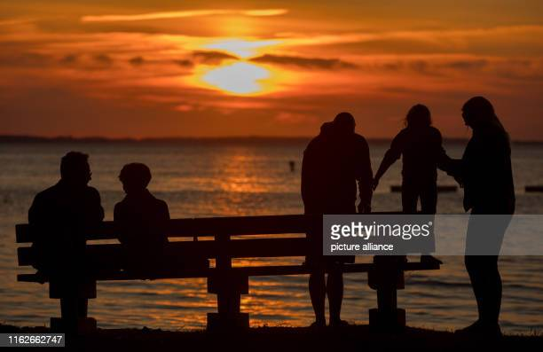 May 2019, Mecklenburg-Western Pomerania, Boek: Holidaymakers watch the sunset on the banks of the Müritz. Founded in 1990, the Müritz National Park...