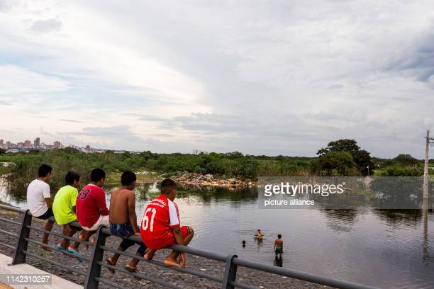 May 2019, Paraguay, Asuncion: Young people sit on a bridge and look at a flooded plain. According to official figures 000 people had to be evacuated...