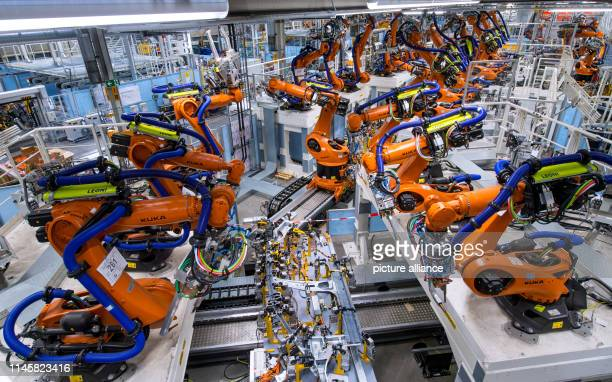 May 2019, Saxony, Zwickau: Robotic arms can be seen along a new production line for the manufacture of electric vehicles at the Volkswagen Sachsen...