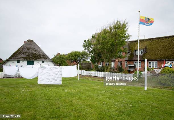 May 2019, Schleswig-Holstein, Dagebüll: Laundry dries in front of a house on the Hallig Langeness. The 11,500 square kilometre Wadden Sea stretches...