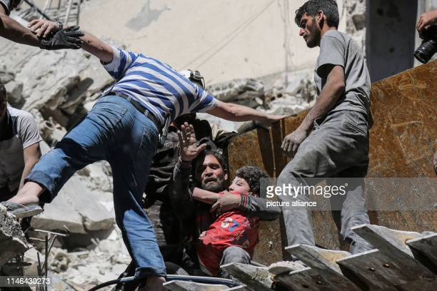 A man hugs a child after he was rescued by the members of the Syrian Civil Defense from the rubble of a building that was damaged in an airstrikeby...