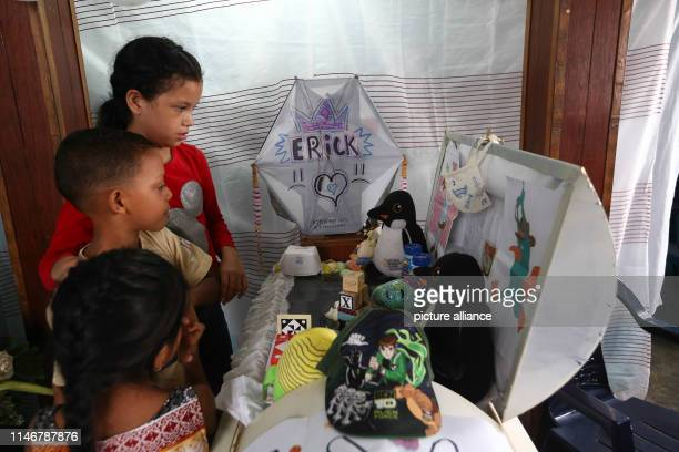 Children observe drawings and toys on the coffin of 11yearold Erick Altuve in his apartment in the Petare district Erick died waiting for a bone...