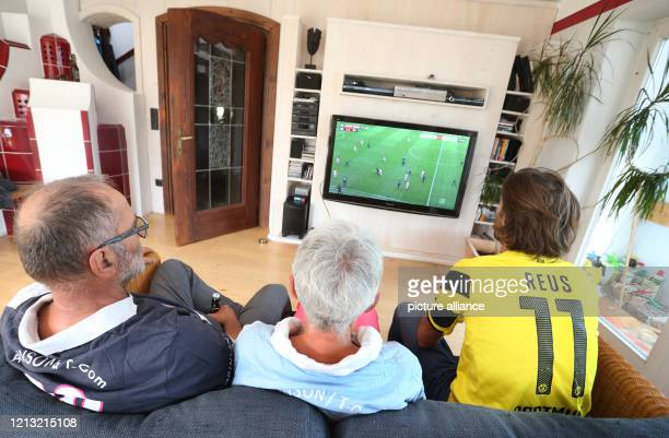 May 2020, Bavaria, Rieden: A family in an apartment watches the conference call of first division matches of the Sky television channel on their...