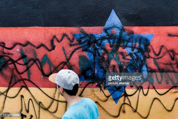 """Young man walks past the destroyed mural by the artist Günther Schäfer at the East Side Gallery. The mural """"Vaterland"""", which shows the..."""