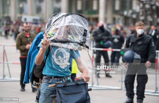 On Alexanderplatz there is a demonstrator with a protective construction and a Q The Q stands for QAnon and is a sign of a conspiracy theory In the...