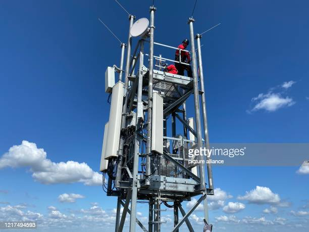 Workers install antennas for the fifth generation of mobile communications on a radio mast in the Berlin district of Schmöckwitz at a height of a...