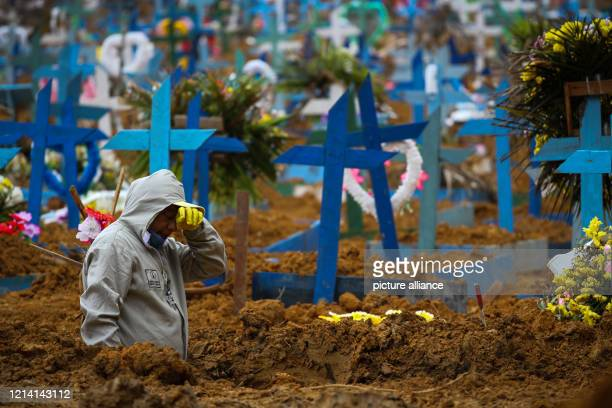 May 2020, Brazil, Manaus: A man works in a mass grave at the cemetery Nossa Senhora Aparecida in Manaus. In Brazil 17 971 patients have died in...