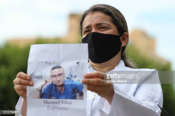 May 2020, Brazil, Manaus: On International Nursing Day, a health worker wearing a black mouthguard holds up the image of a nurse who is said to have...