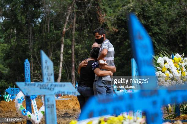 Relatives hug each other at a funeral at the cemetery Nossa Senhora Aparecida in Manaus In Brazil 17 971 patients have died in connection with the...