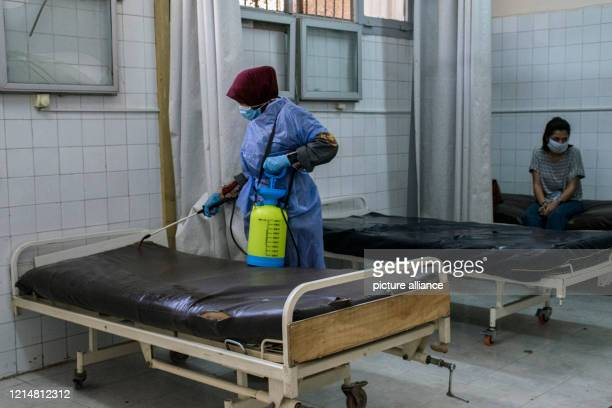 A picture made available on 23 May 2020 shows a medic disinfecting a hospital bed at the 6th Of October Central Hospital which has been transformed...