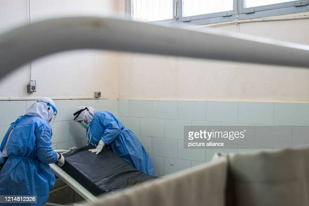 A picture made available on 23 May 2020 shows medics disinfecting a hospital bed at the 6th Of October Central Hospital which has been transformed...