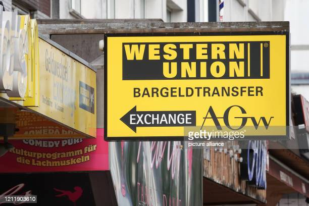 A sign with the logo of Western Union points to a branch of the US provider of worldwide cash transfer on the Reeperbahn on St Pauli Photo Bodo...