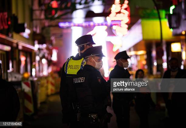 """Police officers walk through the street """"Große Freiheit"""" on the Reeperbahn at the end of a protest action by neighbourhood restaurateurs, club and..."""