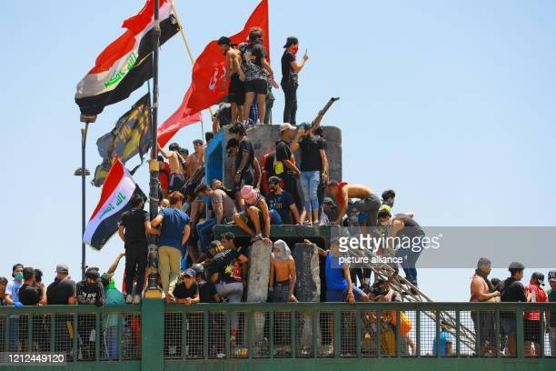 May 2020, Iraq, Baghdad: Demonstrators hold flags as they take part in a protest demanding reforms at Jumhuriya bridge, days after a new government...