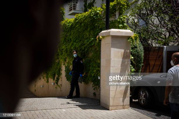 A police officer wears a face mask as he stands outside the residency of the Chinese Ambassador to Israel Du Wei after he was found dead Photo Ilia...