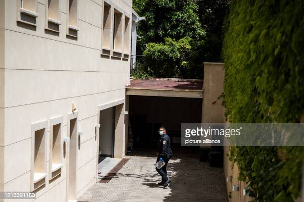 A police officer wears a face mask as he stands inside the back yard of the residency of the Chinese Ambassador to Israel Du Wei after he was found...
