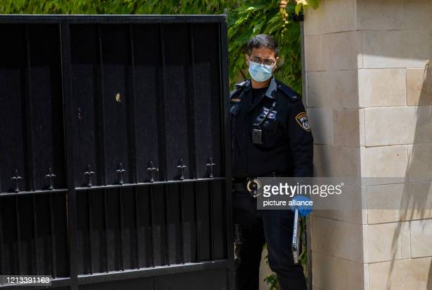 A police officer wears a face mask as he stands inside the residency of the Chinese Ambassador to Israel Du Wei after he was found dead Photo Ilia...
