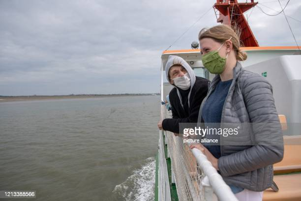May 2020, Lower Saxony, Spiekeroog: Annette and Elsa from Lower Saxony are standing on the ferry to Spiekeroog with mouth protection. Many people...