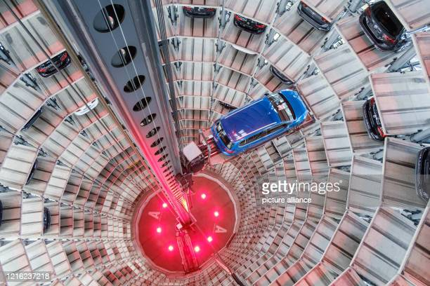 May 2020, Lower Saxony, Wolfsburg: Volkswagen new cars are parked in a car tower in the Autostadt. The Autostadt in Wolfsburg celebrates its 20th...