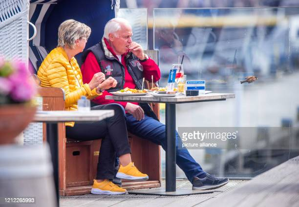 09 May 2020 MecklenburgWestern Pomerania Kühlungsborn A sparrow flies off the table with a piece of French fries Petra and RalfRainer Schmidt from...