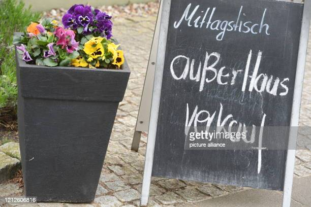 """May 2020, Mecklenburg-Western Pomerania, Koserow: A signboard with the inscription """"Mittagstisch außer Haus verkauf"""" is located at the roadside in..."""