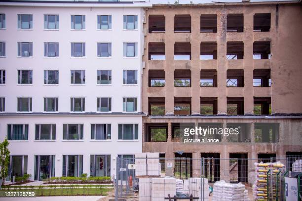 May 2020, Mecklenburg-Western Pomerania, Prora: View of a part of the building still under reconstruction and a house of block 5 in the listed...
